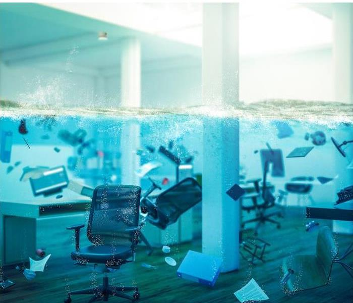 A flooded office with chairs and office equipment floating in the water